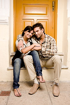 Image of a couple sat on a step outside a property to illustrate prospective tenants.